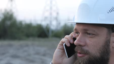 fitter : Station technical director in a white helmet stands near the power station and talking on the phone with the workers.