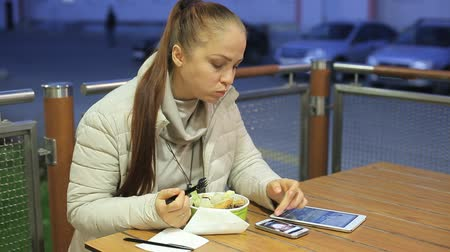 fejlövés : a middle-aged Caucasian woman is sitting at a table in a summer cafe on a cold evening, eating vegetable salad and fried chicken, next to her is a smartphone and a tablet.