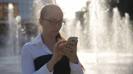 liga : young woman Caucasian appearance in optical glasses in the Park near the fountain with smartphone in hand. Vídeos