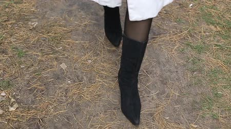 calças justas : womens feet in suede autumn boots and black pantyhose on a Park path background Vídeos