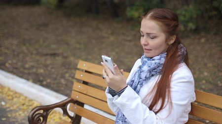 liga : red-haired middle-aged woman with a smartphone in her hand sits on a bench in the Park and communicates in social networks