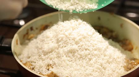 frypan : the housewife adds the rice with grilled meat and cooks risotto on a gas stove at home in the kitchen