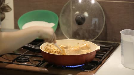 white onion : the housewife adds the rice with grilled meat and cooks risotto on a gas stove at home in the kitchen