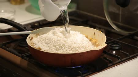 frypan : the housewife adds water to the rice and grilled meat and cooks risotto on a gas stove at home in the kitchen Stock Footage