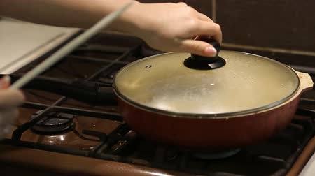 white onion : housewife tries cooked pilaf at home in the kitchen Stock Footage