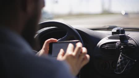 A man with a beard paves the route on a smartphone while sitting in the car