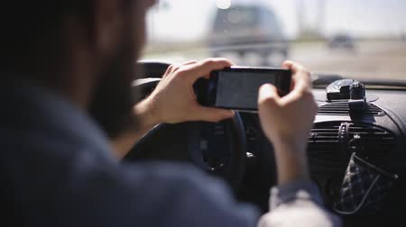 titular : A man with a beard paves the route on a smartphone while sitting in the car