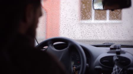 hátsó megvilágítású : A man with a beard sits down in the car and goes. Rainy weathe Stock mozgókép