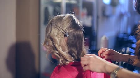 Professional hairdresser doing hairstyle with bun and curls for beautiful healthy hair
