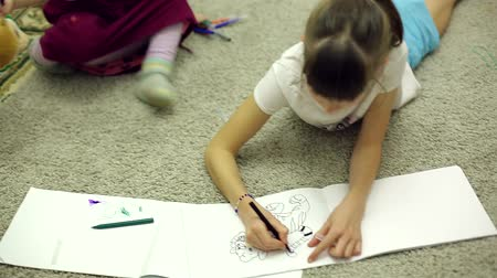 keçe : girls draw markers in the album lying on the floor in the room