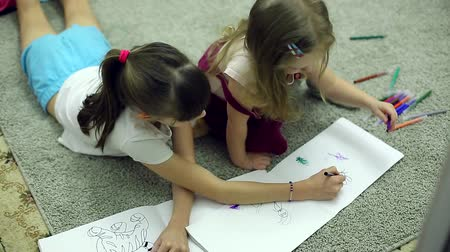 marker : girls draw markers in the album lying on the floor in the room