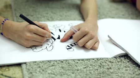 ipuçları : girls draw markers in the album lying on the floor in the room