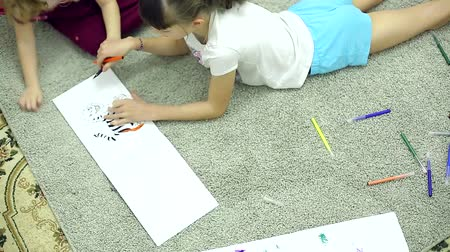 small pen : girls draw markers in the album lying on the floor in the room