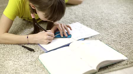 fed : teen girl doing homework sitting on the carpet in her room Stock Footage