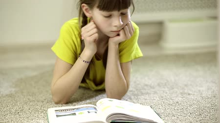 livros didáticos : teen girl doing homework sitting on the carpet in her room Stock Footage