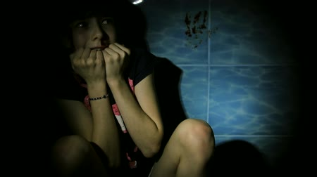 испуг : teen girl with blood on her face hiding in bathroom, domestic violence