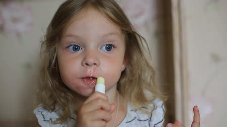 smudged : a little two-year-old girl paints her lips with her mothers lipstick.