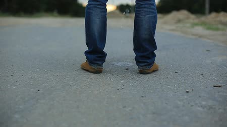znečištěné : a man pees on the asphalt country highway. male legs in jeans and brown shoes.