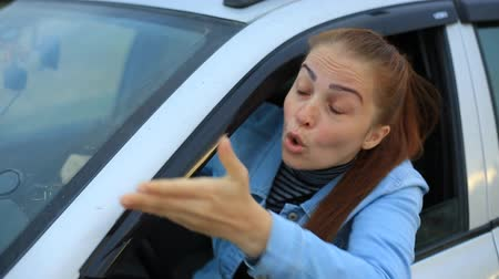 furioso : Middle aged woman sits in the car and complains on traffic situation - car stands on the verge of road in countryside Stock Footage