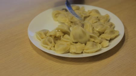 pelmeni : man eating dumplings with beef at home in the kitchen