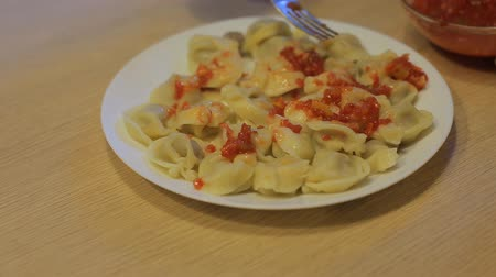 gulasz : man eating dumplings with beef and tomato sauce at home in the kitchen