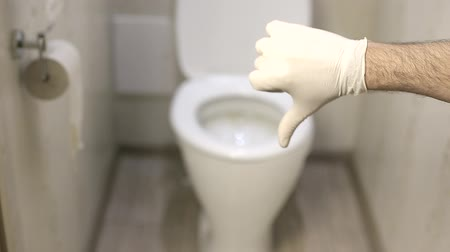 único : man is showing thumb down with white latex gloves on the background of toilet