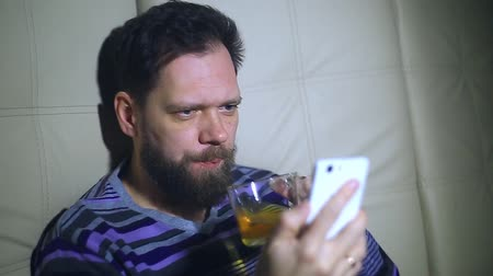 call out : a bearded man watching news on the smartphones screen and drinking tea and responding to the call. From a surprise spits out tea from his mouth.
