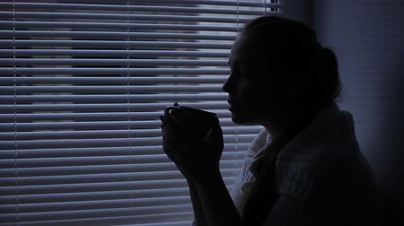 oneperson : woman holding a Cup of tea and drinking sitting around the window Stock Footage