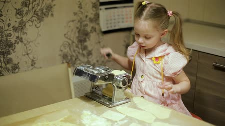 little girl making pasta in the kitchen