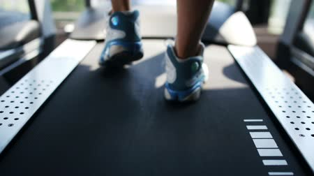 tornaterem : A young sporty men booted in sneakers walking on the treadmill in the gym