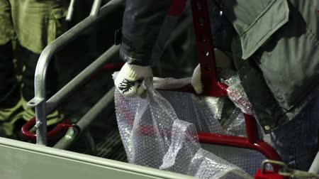 szermierka : worker in white gloves unpacks part of the fence from the Bubblewrap and passes it to another worker