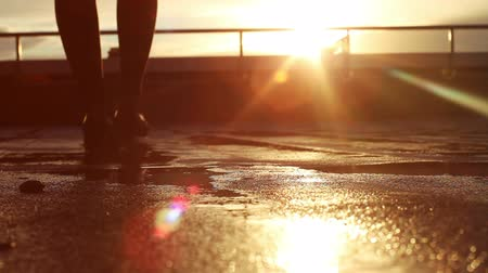 andar : Legs of pretty young woman walking on the sidewalk after a rain in the sunset