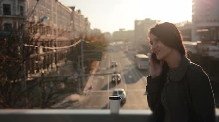 young pretty  woman talking on the phone on a city bridge on the Sunset Stock Footage