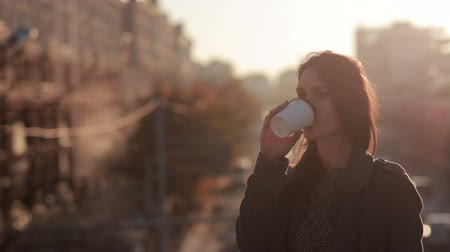 кофе : Beautiful girl drinking coffee on the street looking at the camera Стоковые видеозаписи