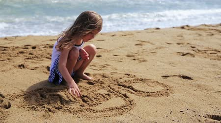 plaz : Little girl drawing and jumps on the shore of a sand beach. Dostupné videozáznamy