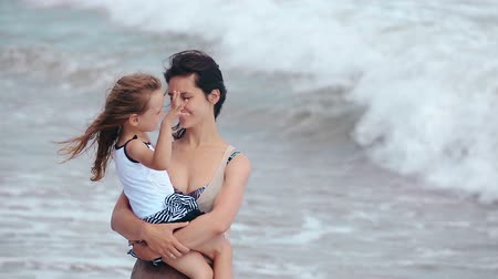 ventoso : Happy smiling family mother and daughter pointing finger and hug kissing on the sea beach windy evening