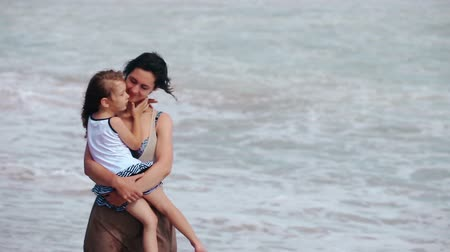 little finger : Happy smiling family mother and daughter pointing finger and hug kissing on the sea beach windy evening
