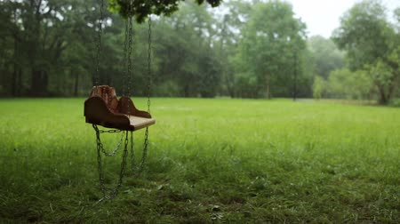 üres : Empty wooden swing swaying slowly in the rain in a park