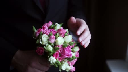 bouquets : groom holds a wedding bouquet in his hands at home