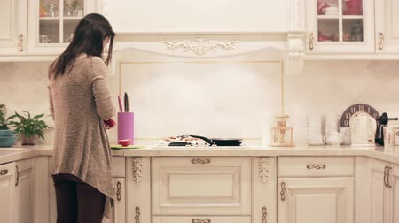 kitchen furniture : girl preparing a meal in the kitchen. time lapse