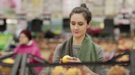 recados : Young woman chooses ripe oranges on store shelves.
