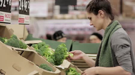 recados : Young woman chooses cabbage on store shelves.