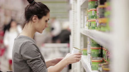 consumismo : Young woman chooses canned food in the store Vídeos