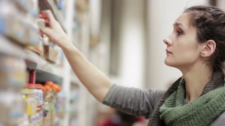 manifatura : Young woman chooses baby food in the supermarket Stok Video