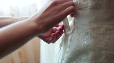 nevěsta : Bridesmaids buttoning on wedding dress