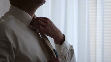 аккуратный : close-up of a man straightens his tie