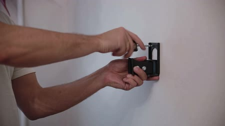 dowel : Man installs the holder bracket  on the wall