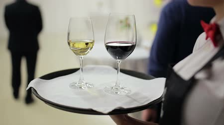 формальный : waiter holding a tray with glasses of wine