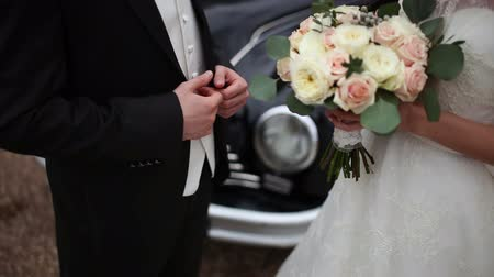 evli : bride with a bouquet and groom near a retro car Stok Video