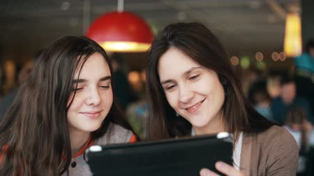 smích : two girls sisters using tablet talking in cafe